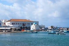 Mykonos, Grèce - 4 mai 2010 : bateaux de pêche sur la plage de mer Village au bord de la mer sur le ciel nuageux Église et maison Photographie stock libre de droits