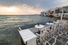 MYKONOS, GRÉCIA - EM MAIO DE 2018: Opinião do por do sol do café do embarkment de pouco distrito de Veneza na cidade de Mykonos C Foto de Stock Royalty Free