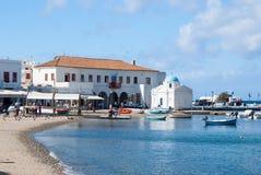 Mykonos, Grecia - 4 de mayo de 2010: iglesia y casas en el pueblo de la costa de mar en la playa en el cielo azul Dos barcos rast Foto de archivo