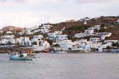 Mykonos Grecja, Maj, - 04, 2010: domy przy dennego wybrzeża morzem z statkami na góra krajobrazie Wioska rybacka przy nadmorski d Fotografia Stock