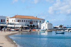Mykonos Grecja, Maj, - 04, 2010: kościół i domy przy dennego wybrzeża wioską przy nadmorski na niebieskim niebie łodzie poławiają Zdjęcie Stock