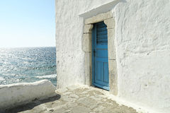 Mykonos, Greece – A blue door on a whitewashed wall. The entrance to one of the five churches that form The Church of Panagia Paraportiani royalty free stock photos