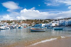 Mykonos, Greece - May 04, 2010: boats at sea beach. Sea coast on cloudy blue sky. Mediterranean village with houses on. Mountain landscape. Summer vacation on royalty free stock photo