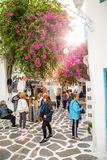 Mykonos, Greece - 17.10.2018: People on street with Traditional houses with blue doors and windows in the narrow streets stock photos