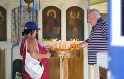 Mykonos, Greece, 11 September 2018, Tourists perform the classic religious gesture of candle lighting in a church. In the Cyclades stock photo