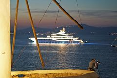 Mykonos, Greece, 7 September 2018, Typical scene that you can admire in the Cyclades with tourists who photograph and luxurious. Yachts on the background stock photos