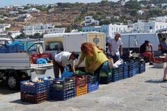 Mykonos Grekland - Augusti 13 2016: Lokala försäljareförsäljningsprodukter på kustlinjen royaltyfri foto