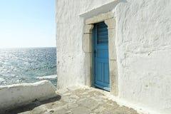 """Mykonos, Griechenland-†""""eine blaue Tür auf einer rehabilitierten Wand Lizenzfreie Stockfotos"""