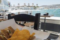 Mykonos, Griekenland - Augustus 14 2016: Ontbijt met een mening van de windmolens Royalty-vrije Stock Afbeeldingen