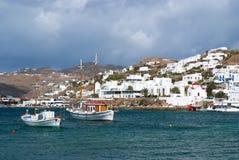Mykonos, Griekenland - Mei 04, 2010: De visserij van dorp bij kust op bewolkte hemel Boten van de huizen de op zee kust in blauwe Royalty-vrije Stock Fotografie