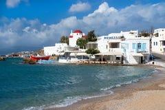 Mykonos, Griekenland - Mei 04, 2010: overzees strand op bewolkte blauwe hemel Kerk en huizen van de dorps de de op zee kust bij k Stock Afbeeldingen