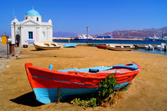 Mykonos harbor. Old boat and traditional blue dome church on the shore of Mykonos island, Greece Stock Image