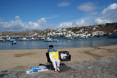 Mykonos island, Greece. Painter selling pictures at the Mykonos harbor royalty free stock images