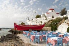 Mykonos taverna and church. Mykonos beach taverna with decorative boat and red cupola church royalty free stock photos