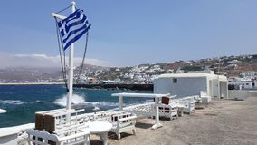 Mykonos Town, Greece - Greek flag-waving  at summer by the old port. stock video footage