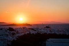 Mykonos town at sunset with cruise liner in background Stock Photos