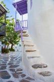 Mykonos uliczny widok z białymi schodkami, drzewami i purpurowym balkonem, Grecja Zdjęcia Stock