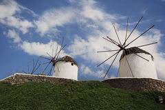 Mykonos Windmills. On a clear summer day with green grass and blue sky. Mykonos, Greece royalty free stock photo