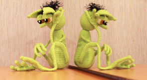 Mymra in sorrow. Knitted toy mirror reflection Royalty Free Stock Photo