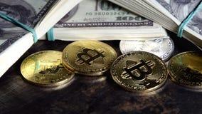 Mynt av bitcoin på sedlar av hundra dollar räkningar i grupperingar rotera på det mörka grungeskrivbordet arkivfilmer