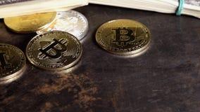Mynt av bitcoin på sedlar av hundra dollar räkningar i grupperingar rotera på det mörka grungeskrivbordet lager videofilmer