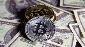 Mynt av bitcoin på sedlar av hundra dollar räkningar i grupperingar rotera på det mörka grungeskrivbordet stock video