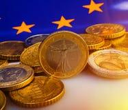 Mynt av euroet och eurocent mot bakgrunden av flaggan Fotografering för Bildbyråer