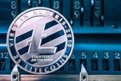 Mynt av litecoin på bakgrunden av nummer som tillfogar maskinen royaltyfri bild
