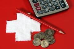 Mynt av Schweiz med räknemaskinen och blyertspennan på det röda PVC-lädret med vit korsar tyg som sätts som en schweizisk nationf royaltyfri foto