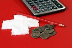 Mynt av Schweiz med räknemaskinen och blyertspennan på det röda PVC-lädret med vit korsar tyg som sätts som en schweizisk nationf Royaltyfria Bilder