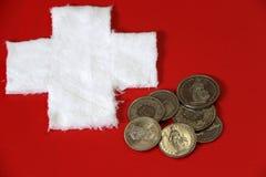 Mynt av Schweiz på det röda PVC-lädret med vit korsar tyg som sätts som en schweizisk nationflagga Arkivbilder