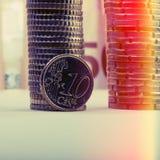 Mynt av tio eurocent på bakgrunden av vikta mynt och ett p Royaltyfri Foto