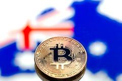 Mynt Bitcoin, mot bakgrunden av Australien och den australiska flaggan, begrepp av faktiska pengar, närbild pengar för huset för  Arkivfoto