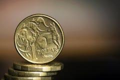 Mynt för australisk dollar över suddig bakgrund med Copyspace arkivbild