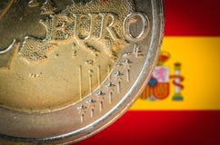 Mynt för euro 2 med en suddig flagga av Spanien på bakgrunden royaltyfria bilder