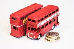 Mynt för London buss och 1 pund Arkivfoto