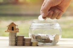 Mynt för pengar för kvinna` s hand satta i glasflaskan för räddning och donationbegreppet för köpande hus Arkivbild