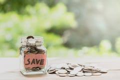 Mynt i den glass kruset för pengarbesparing Sparande finansiellt begrepp för pengar Arkivbilder