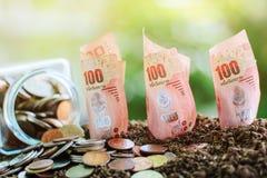 Mynt i den glass kruset och sedeln, 100 baht thailändsk valutagrowi Arkivfoto