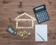 Mynt i det formade huset, räknemaskinpenna och anteckningsbok Arkivfoton