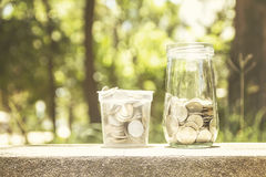 Mynt i en glass krus Arkivfoton