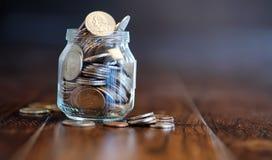 Mynt i en glass krus på ett trägolv Fick- besparingar från mynt Royaltyfria Foton