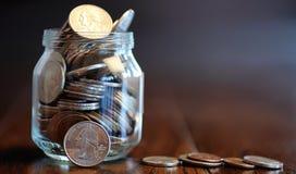 Mynt i en glass krus på ett trägolv Fick- besparingar från mynt Arkivfoton