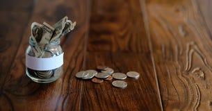 Mynt i en glass krus på ett trägolv Fick- besparingar från mynt Arkivfoto