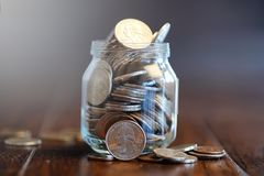 Mynt i en glass krus på ett trägolv Fick- besparingar från mynt Royaltyfri Bild