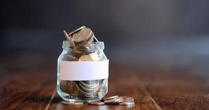 Mynt i en glass krus på ett trägolv Fick- besparingar från mynt Royaltyfri Foto