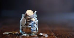 Mynt i en glass krus på ett trägolv Fick- besparingar från mynt Royaltyfria Bilder