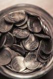 Mynt i en krusflaska arkivbild