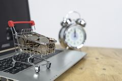 Mynt i en spårvagn på ett bärbar datortangentbord och ringklocka Idéer om online-shopping, online-shopping är en form av elektron arkivbilder