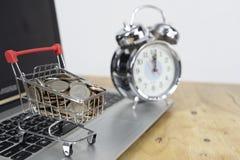 Mynt i en spårvagn på ett bärbar datortangentbord och ringklocka Idéer om online-shopping, online-shopping är en form av elektron royaltyfria foton